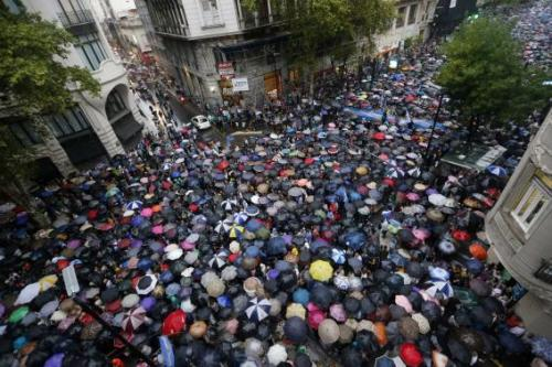 Protesters holding umbrellas to shield themselves from the rain take part in a silent march to honour late state investigator Alberto Nisman in Buenos Aires